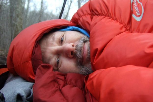 Photograph of Gary Allman snuggled up in a Montbell Super Spiral Down Hugger sleeping bag.