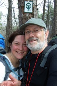 Man and woman wearing backpacks while hiking the Berryman Trail in Mark Twain National Forest.
