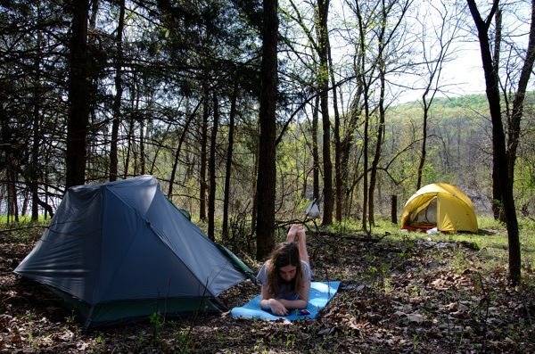 Teen girl lying by her tent reading a book on her iPod while on a camping trip.