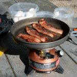 Picture of bacon sizzling onto of a Coleman Exponent stove