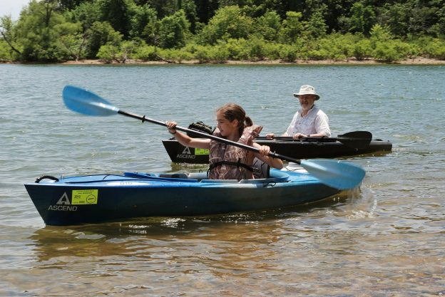 Teen girl paddling her kayak on Stockton Lake while her father watches from his kayak.