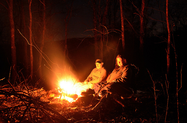 A couple sitting around a campfire at night on at Piney Creek Wilderness on Table Rock Lake.