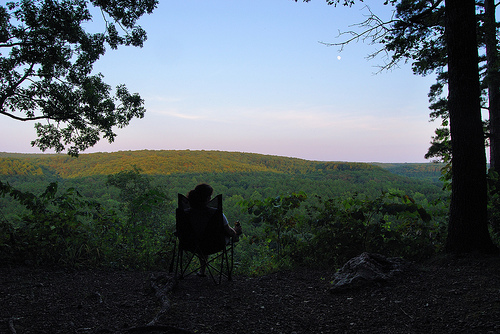 Woman seated in camp chair, watching night fall over a valley at Red Bluff Campground.