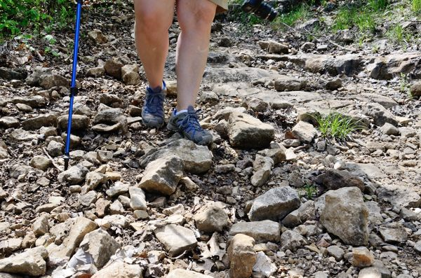 Woman wearing shorts and trail runner shoes hikes downhill on very rough terrain in the Ozarks using a trekking pole for stability.