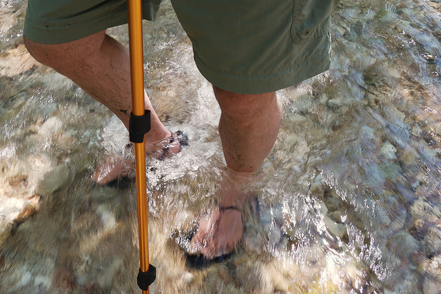 A man wearing shorts and hiking huaraches crossing a creek with running water while using a hiking pole for balance.