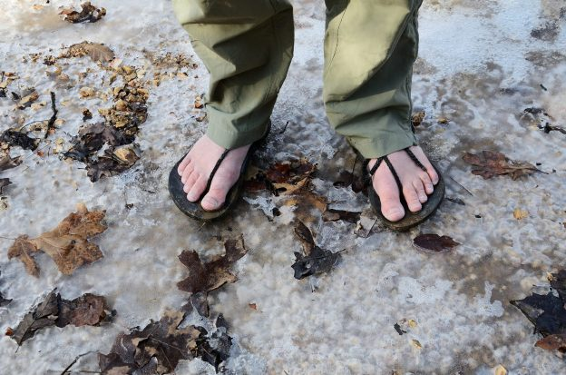 Bare feet and hiking huaraches on frozen ground