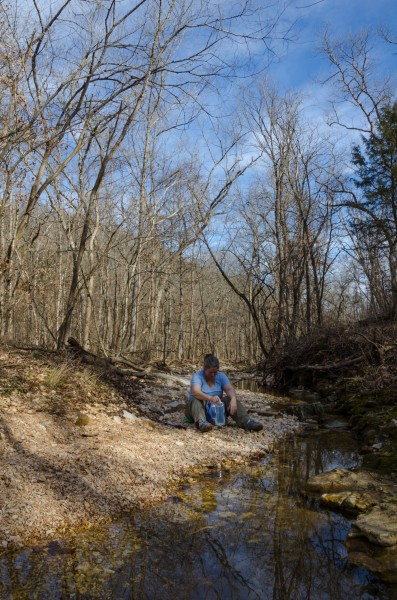 Ginger takes advantage of my photo-session to sit down by a creek on the White trail at Busiek and take a drink. January 30, 2016 | Copyright © 2016, all rights reserved