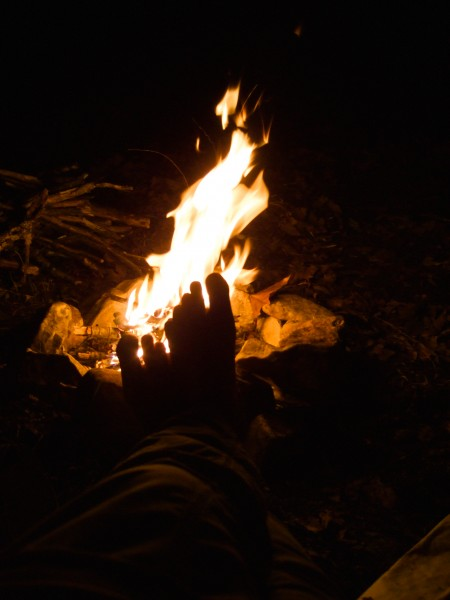 Gary warming his feet by the campfire